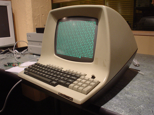 An image showing a terminal and a computer in the early days of computing.