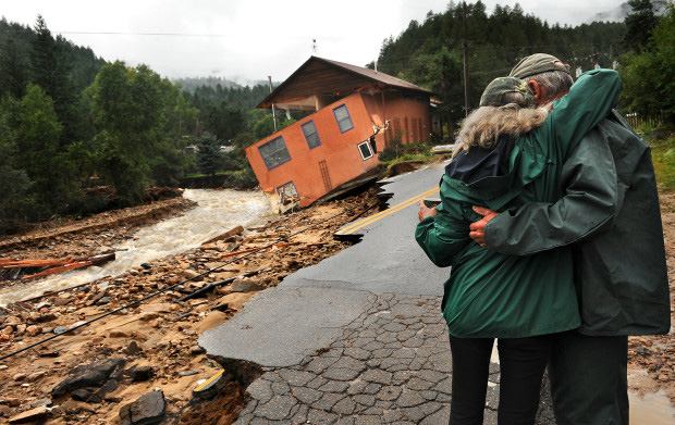 An emotional couple looks on at a home destroyed by the floods near Jamestown, Colorado..